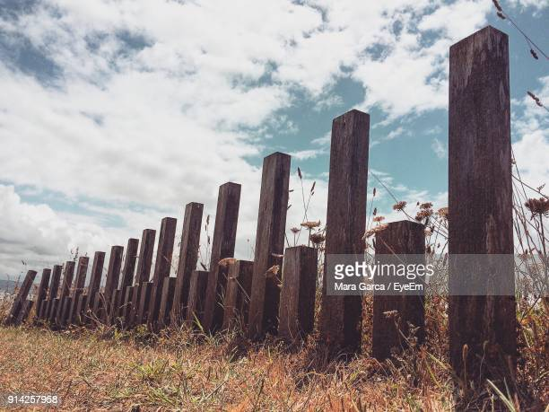 Wooden Posts Against Cloudy Sky