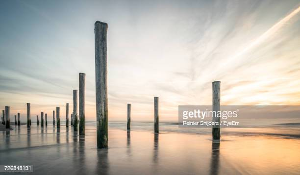 Wooden Posts Amidst Sea At Beach Against Cloudy Sky During Sunset