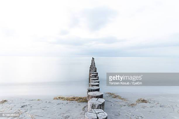 Wooden Posts At Beach Leading Towards Sea Against Sky