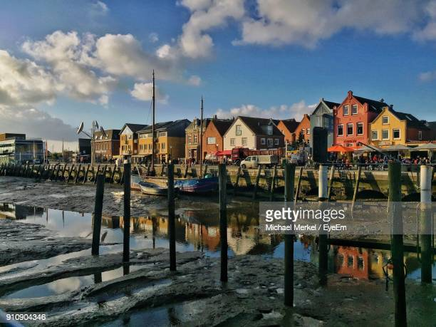 wooden posts at harbor in city against sky - husum stock-fotos und bilder