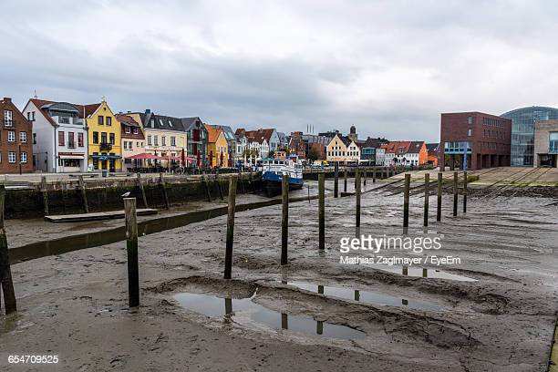 wooden posts by buildings against sky in city - husum stock-fotos und bilder