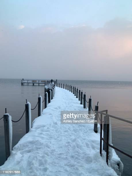 wooden posts in sea against sky during winter - レイクフォレスト ストックフォトと画像