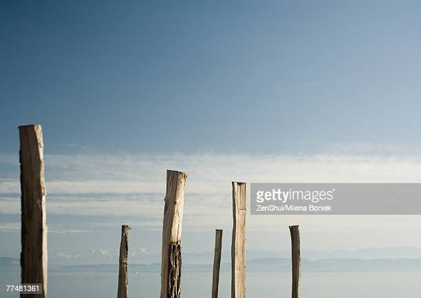 Wooden posts, lake and mountains in background