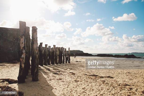 Wooden Posts On Sand At Beach Against Sky