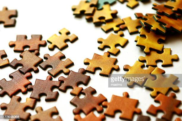 Wooden puzzle pieces scattered on white background