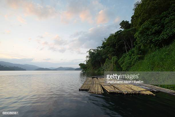 Wooden Rafts Moored On Lake By Trees Against Cloudy Sky