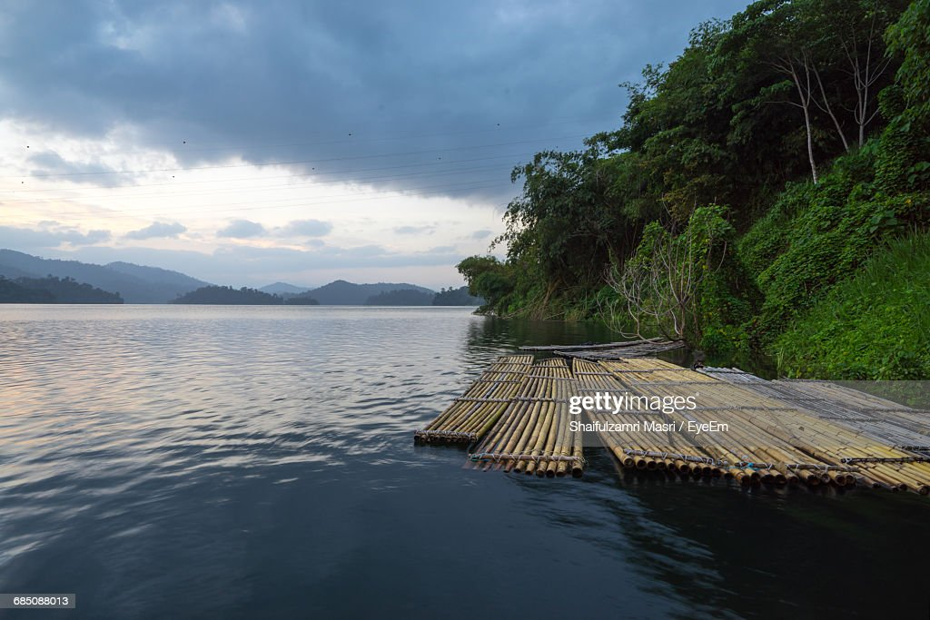 Wooden Rafts Moored On Lake By Trees Against Cloudy Sky : Stockfoto