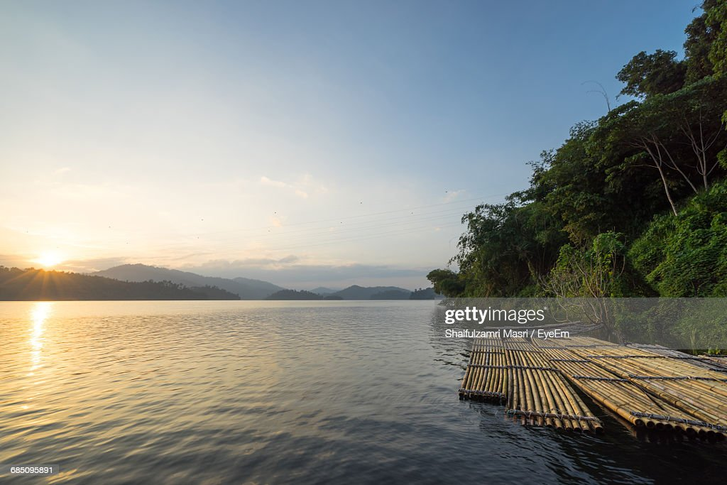 Wooden Rafts Moored On Lake By Trees Against Cloudy Sky : Stock-Foto