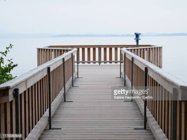 wooden railing on beach against clear sky - sabine hauswirth stock pictures, royalty-free photos & images