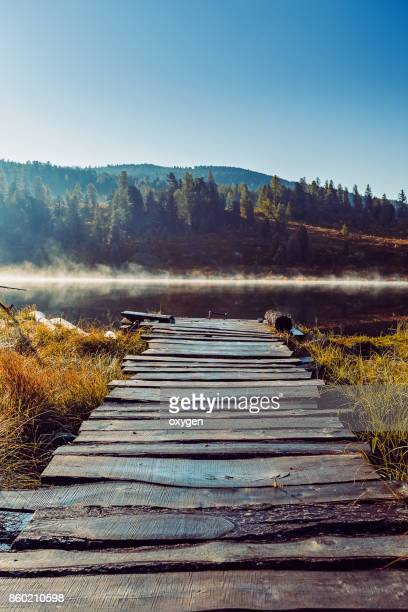 Wooden road to lake on morning sunshine on Altai mountain, Ulagan. Russia