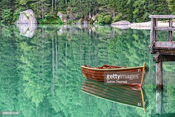 wooden rowing boat at braies lake - dolomite alps, south tyrol, italy - エメラルドグリーン ストックフォトと画像