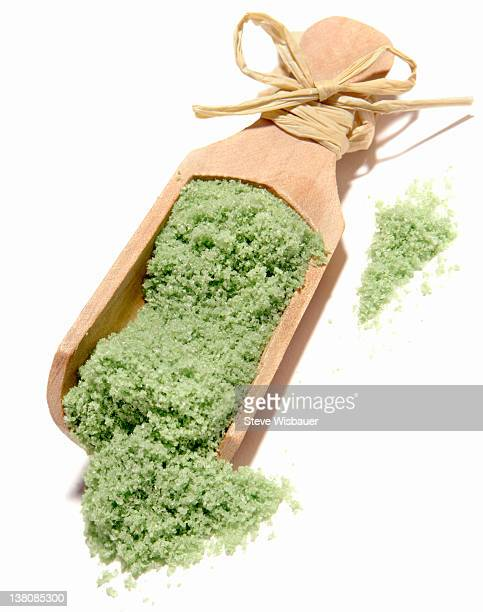 A wooden scoop full of green bath salts
