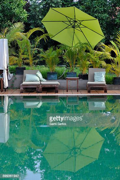Wooden seats and umbrella reflected in pool, Phnom Penh, Cambodia, Southeast Asia