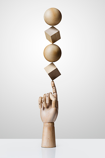 Wooden shapes balancing on a wooden hand - gettyimageskorea