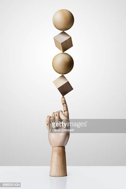 Wooden shapes balancing on a wooden hand
