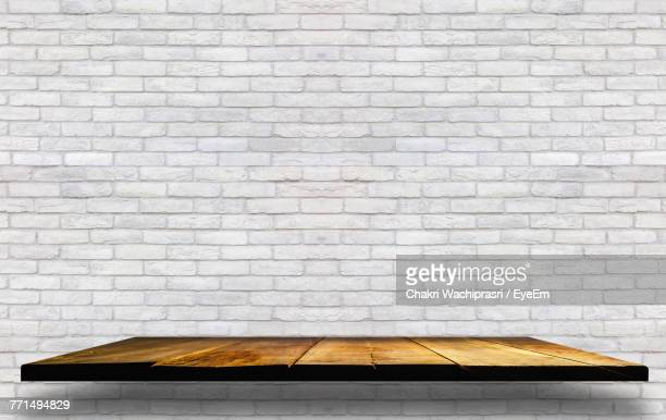 wooden shelf against brick wall - shelf stock pictures, royalty-free photos & images