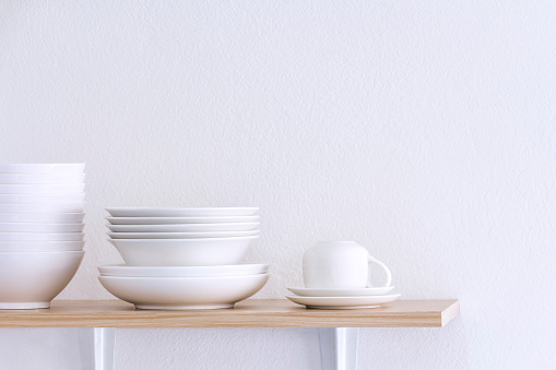 Wooden shelf template isolated on white wall background which on set stacked white bowls and plates as items tableware for decorated interior or montage of your product on shelf with copy space. 1090949036
