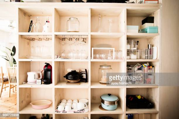 wooden shelves with dishes arranged - storage compartment stock pictures, royalty-free photos & images