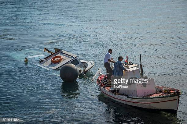 A wooden ship carrying migrants sinks after colliding with a Greek coast guard boat near the Greek island of Lesbos on October 15 2015 Eight migrants...