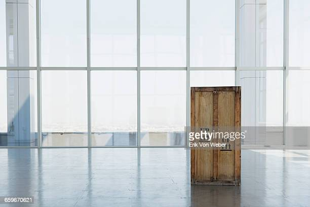 wooden shipping crate in large empty office space - crate stock pictures, royalty-free photos & images