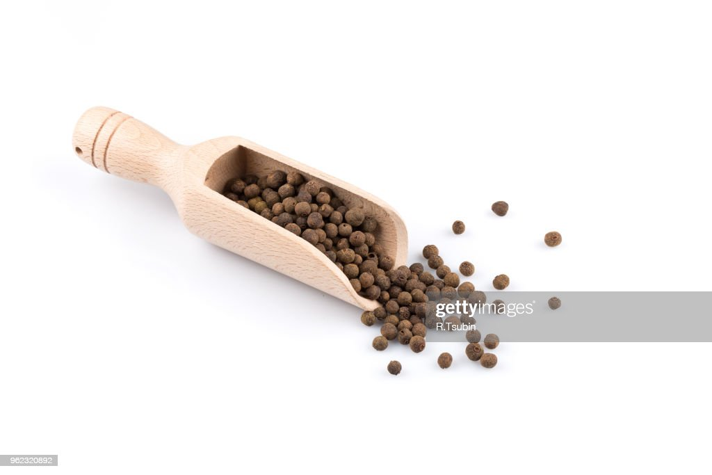 Wooden shovel with large black peppercorn scattered from it : Foto de stock