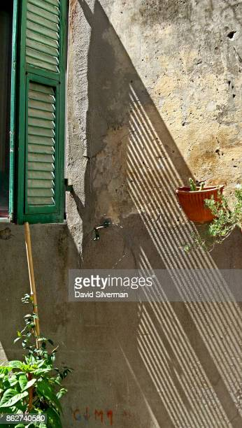 Wooden shutters cast their shadow on a wall on July 22 2015 in the medieval village of Pitigliano in the Grosseto province of Tuscany Italy Tuscany...