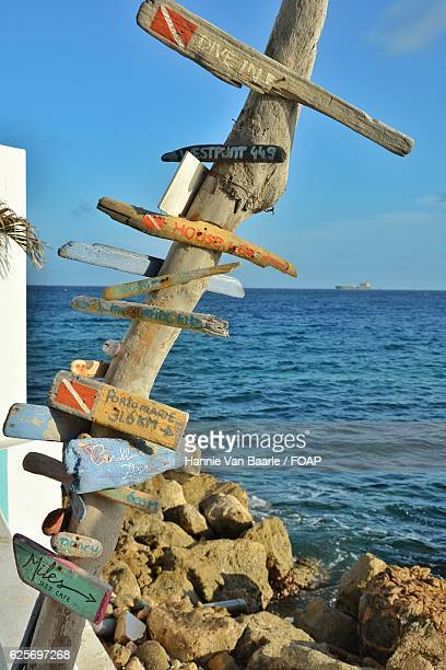 Wooden sign board in front of sea