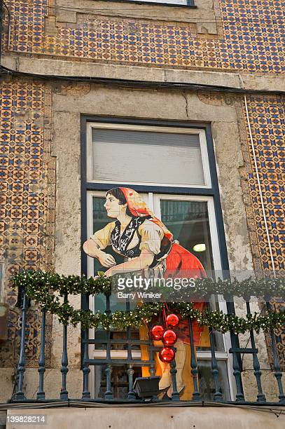 Wooden sign depicting a woman on balcony, at Christmastime, Lisbon, Portugal
