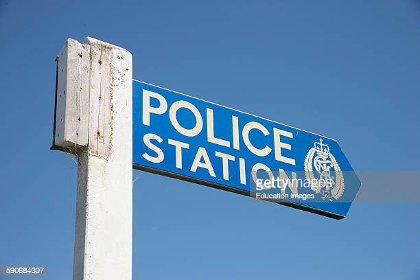 Wooden sign post pointing towards Police Station New Zealand