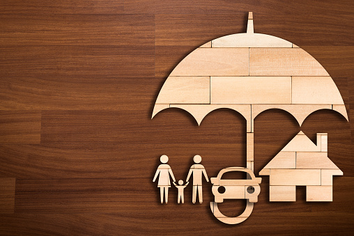 Wooden silhouette of family under umbrella - Concept of Insurance 897545934