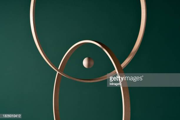 a wooden sphere in the center of intersected rings - image stock pictures, royalty-free photos & images