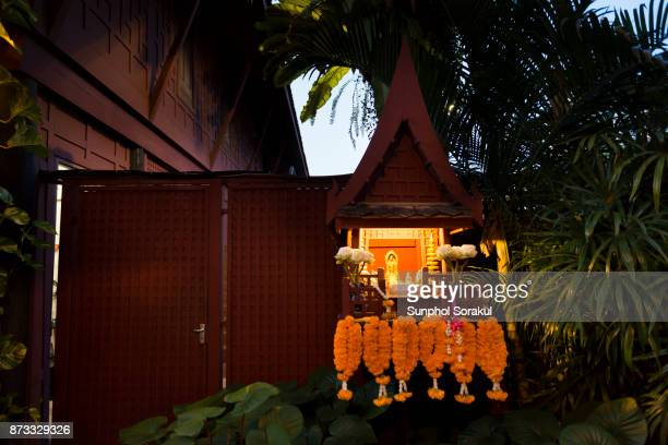 A wooden spirit house illuminates with flower garlands hanging