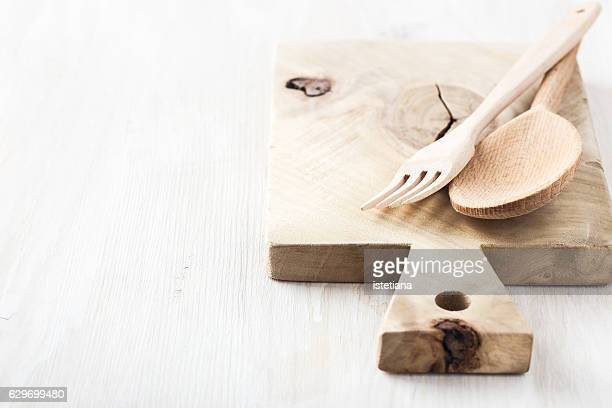 Wooden spoon and fork on white table with copy space