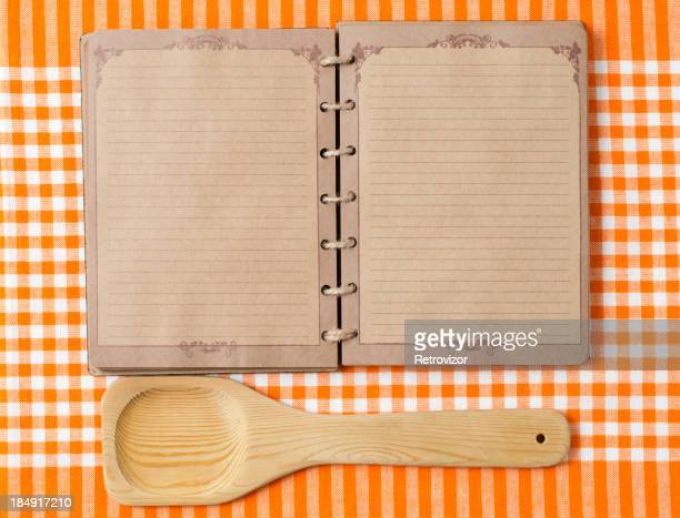 Wooden spoon and old notebook on orange tableclot