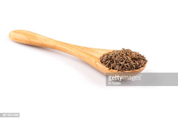 Wooden spoon and pile of cumin seeds isolated on white background