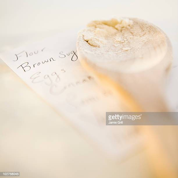Wooden spoon on top of shopping list