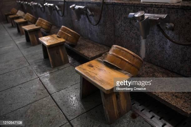 wooden stools inside a japanese onsen - 銭湯 ストックフォトと画像