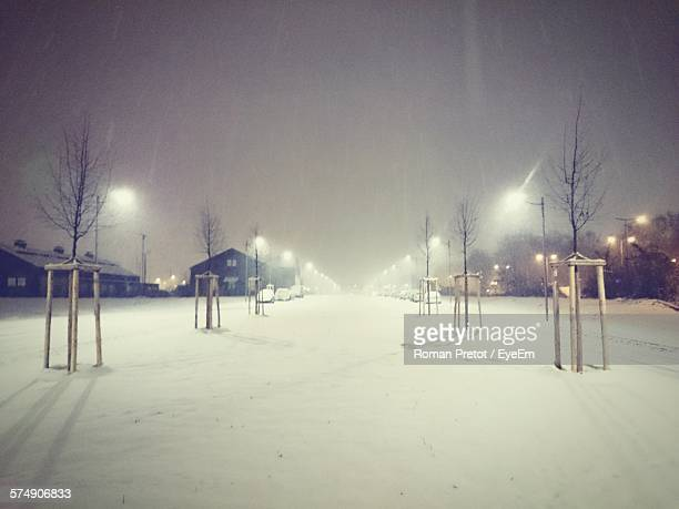 wooden structure on snow covered field against sky at night - roman pretot stock-fotos und bilder