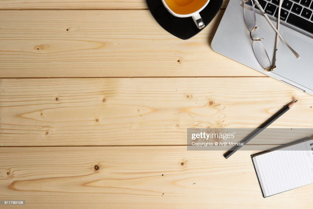 wooden surface diy table top view with office articles, laptop, tea cup : Stock Photo