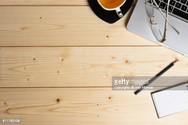 wooden surface diy table top view with office articles, laptop, tea cup