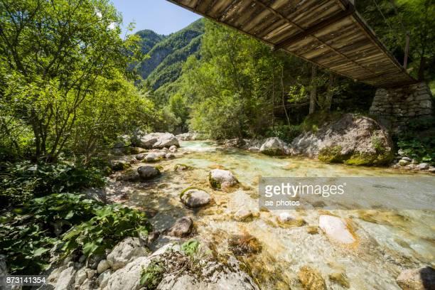 Hölzerne Hängebrücke über Soča unter blauem Himmel im Sommer