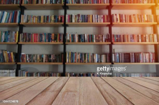 wooden table against bookshelf in library - nah stock-fotos und bilder