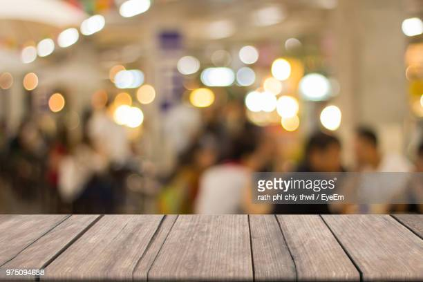 wooden table against illuminated lights - incidental people stock pictures, royalty-free photos & images