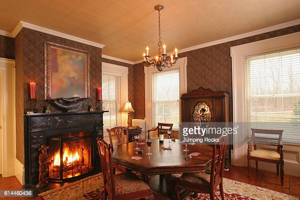 Wooden table and chairs in front of fireplace in lit fire