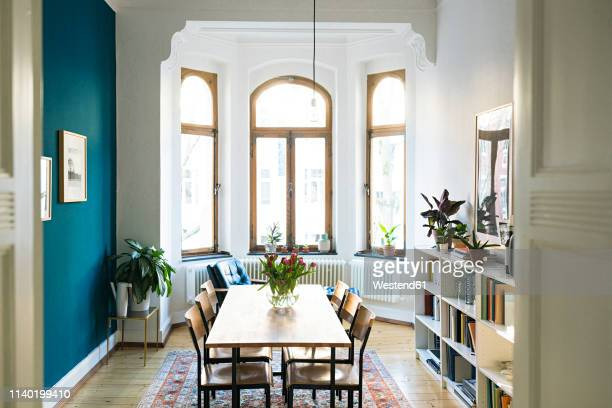 wooden table and chairs in modern living room with large window front in stylish apartment - dining room stock pictures, royalty-free photos & images