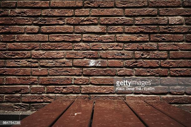 Wooden Table Beside Brick Wall