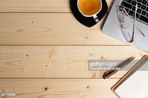 Wooden table from above with laptop keyboard, green tea cup, notepad, pen and copy space