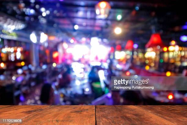 wooden table in front of abstract blurred background of resturant lights - bar stock pictures, royalty-free photos & images