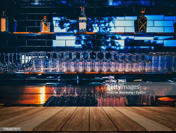 wooden table in front of abstract blurred restaurant lights background of bar - pub stock pictures, royalty-free photos & images
