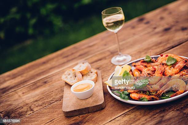 Wooden table outdoors with barbecued prawns and white wine